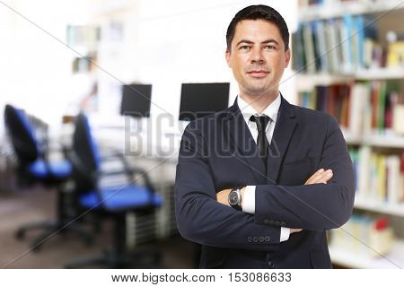 Male librarian on blurred reading room background