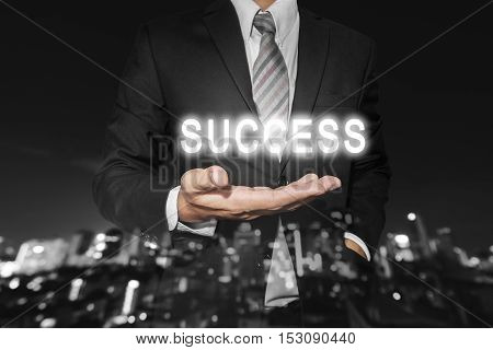 Businessman with bright SUCCESS text on hand, with defocus Bokeh night city background, business success