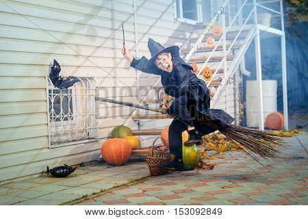 A boy in a costume of wizard flying on a broom with his magic wand. Trick or treat. Halloween celebration.
