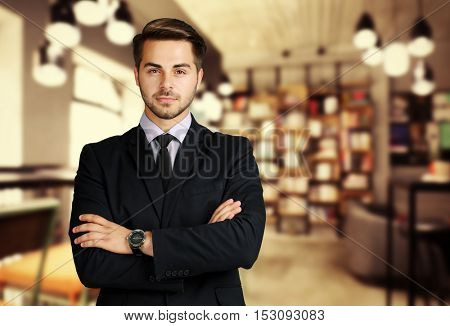 Young male librarian on blurred reading room background