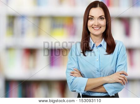 Young female librarian on blurred book shelves background