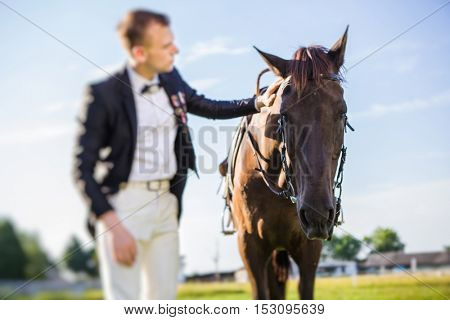 well-dressed man standing by horse on field
