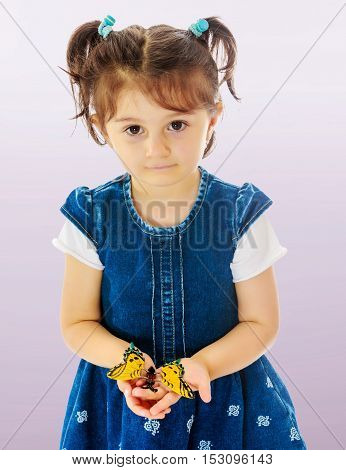 Adorable little girl with short pigtails on her head, holding a large butterfly, close-up.Not a purple gradient background.