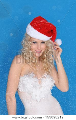 Beautiful woman in Santa hat and snow on blue background