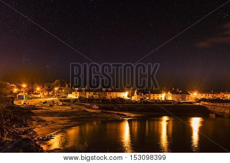 Craster Village at night, with stars above on the Northumberland Coast, with just a hint of the Aurora Borealis