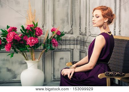 Woman in blue evening gown seated looking to the left