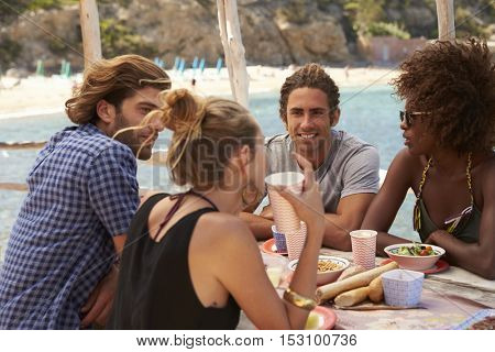 Four friends talking at a table by the sea, side view, Ibiza