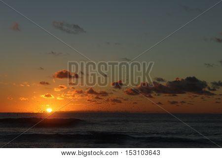 Atardecer entre nubes con sol poniéndose en el mar