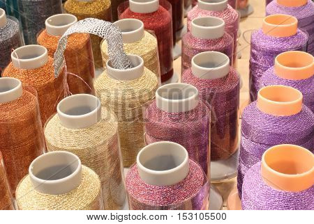 many colorful spools of thread with rhinestones on sale in English haberdashery