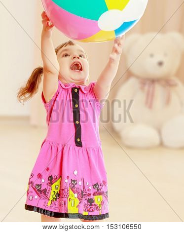 Emotional girl raised her hands up she catches the ball. Close-up.On blurred background children's room in which sits a large Teddy bear.