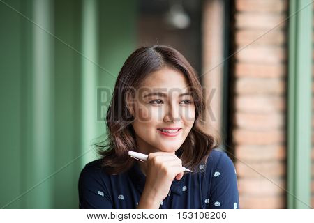 Young beautiful woman in the cafe near the window thinking and writing something.