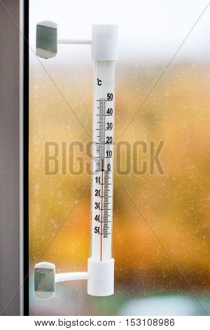 Outdoor Thermometer On Home Window Pane In Autum