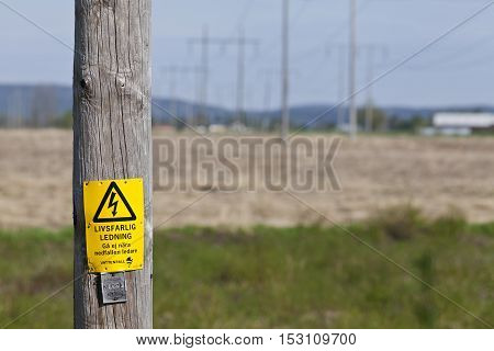 RURAL COUNTY, SWEDEN ON MAY 21. Closeup view on a power line pole, in the landscape on May 21, 2013 in Rural County, Sweden. Poles and wires in the background. Editorial use.