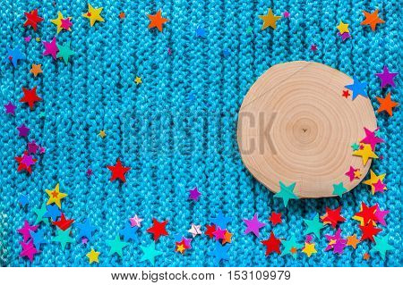 Alder saw cut and the colored stars on a blue knit background. New year and Christmas background.