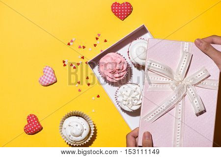 Delicious cupcake with paper box on yellow background