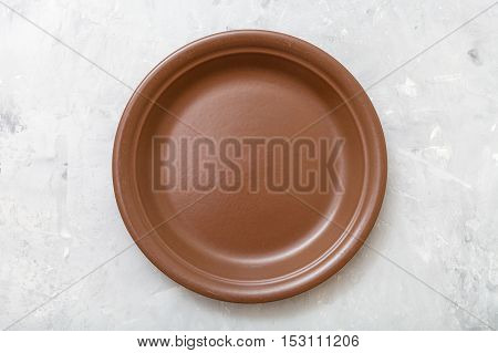 Above View Of One Brown Plate On Gray Concrete