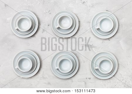 Top View Of Six White Cups And Saucers On Concrete