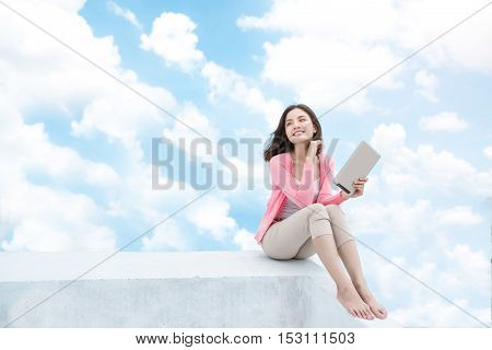 Freedom concept. Enjoyment. Asian young woman relaxing under blue sky on rooftop