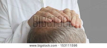 The Gentle Comfort of Hands on Healing  -  Close up of the back of a man's head with a pair of female hands placed on his crown channeling healing energy
