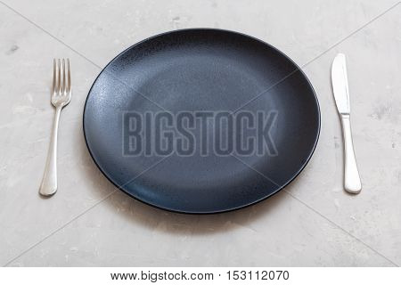 Black Plate With Knife, Spoon On Gray Concrete