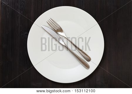 Top View Of White Plate With Flatware On Dark