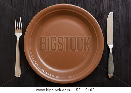 Top View Of Brown Plate With Knife, Spoon On Dark