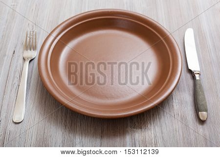 Brown Plate, Knife, Spoon On Gray Brown Table