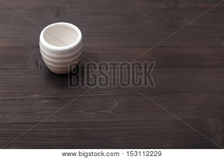 White Cup For Sake On Dark Brown Wooden Board