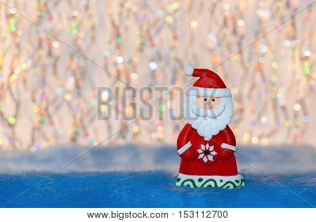 Figurine toy Santa Claus on colorful undulation bokeh background. Suitable for New year or Christmas background.
