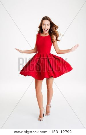 Full length portrait of happy attractive young woman posing in red santa claus costume isolated over white background