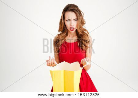 Frustrated upset brunette woman in red dress holding yellow bag and looking at camera isolated on a white background