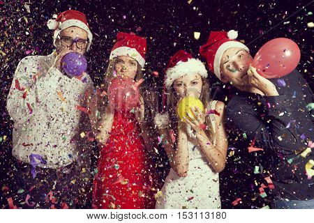 Four young people at New Year's Eve party at midnight blowing colorful balloons and having fun