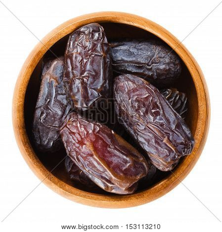 Dried Medjool dates from Morocco in a wooden bowl on white background, also called Mejhool. Large, sweet and succulent fruits of date palms, Phoenix dactylifera. Isolated macro food photo close up.