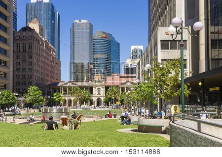 Brisbane, Australia - September 26, 2016: View of people sitting in lawn enjoying the sunshine in Post Office Square in Brisbane during lunchtime with skyline in the background.