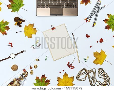 Autumn composition with laptop dry flowers autumn leaves colour pencils brush clips watch toy bear wooden beads and tablet with a blank sheet of paper. Top view on light blue background. Mock up for art work with workplace.