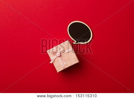 top view of small gift box on red background with wooden black chalk board speech bubble for text