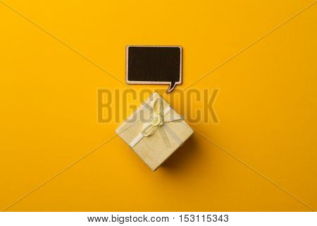 top view of small gift box on yellow background with wooden black chalk board speech bubble for text