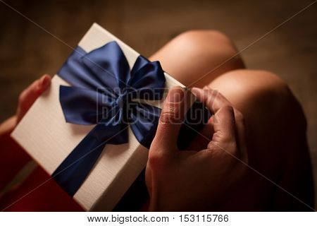 Top view woman opening a present with blue ribbon with three gift boxes inside on her knees
