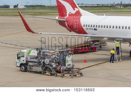 Brisbane, Australia - September 27, 2016: View of workers and fuelling vehicle from Air BP, who specialises in selling aviation fuels, pumping fuel into Qantas aircraft at Brisbane Airport.