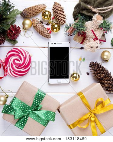 new year background top view: smartphone. Christmas decorations. gifts kraft paper. balls. cones