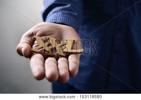 closeup of some wooden letters forming the expression XXL, for extra extra large, in the hand of a young caucasian man
