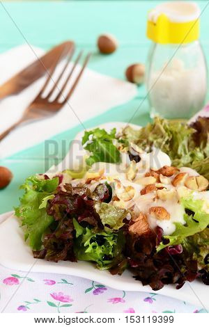 Fresh salad leaves with yogurt and hazelnuts on a plate. Diet salad recipe. Wooden background. Closeup poster