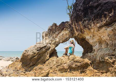 Girl sitting on coastal sea rocks. Well being healthy lifestyle.