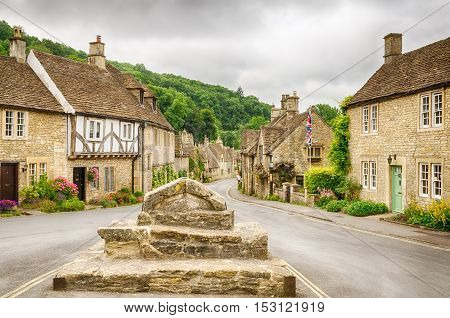 Historic houses in the Cotswold village of Castle Combe, described as the prettiest village in England and a major tourist destination close to the city of Bath and Stonehenge. poster