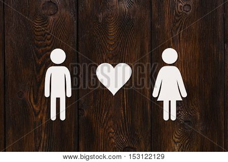 Paper man, woman and heart on dark wooden background. Love relation concept. Abstract conceptual image