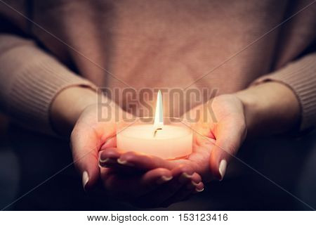 Candle light glowing in woman's hands. Praying, faith, religion concept.