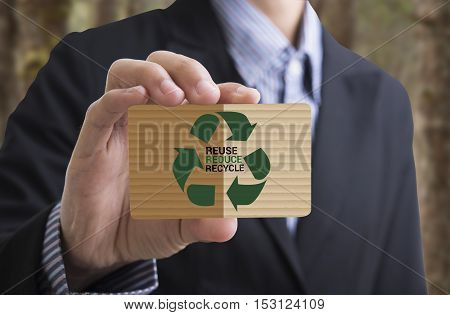 Businessman holding businesscard message recycle reduce reuse.Environmental concept recycle reduce reuse. poster