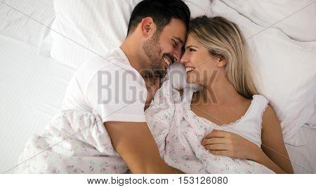 Romantic couple in bed in nightwear smiling