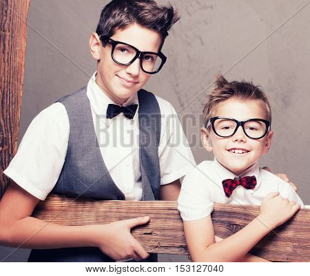 Portrait of two young elegant brothers holding wooden frame looking at camera wearing fashionable eyeglasses and bow tie.
