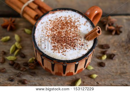 Latte for breakfast with cinnamon cardamom and Dittany on a wooden background